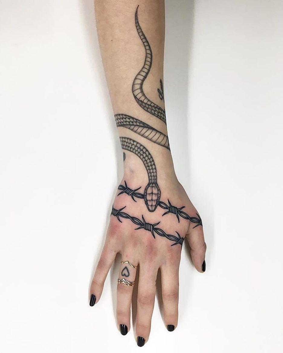 深圳招商海月花园做五金店的容小姐手背荆棘蛇纹身图案